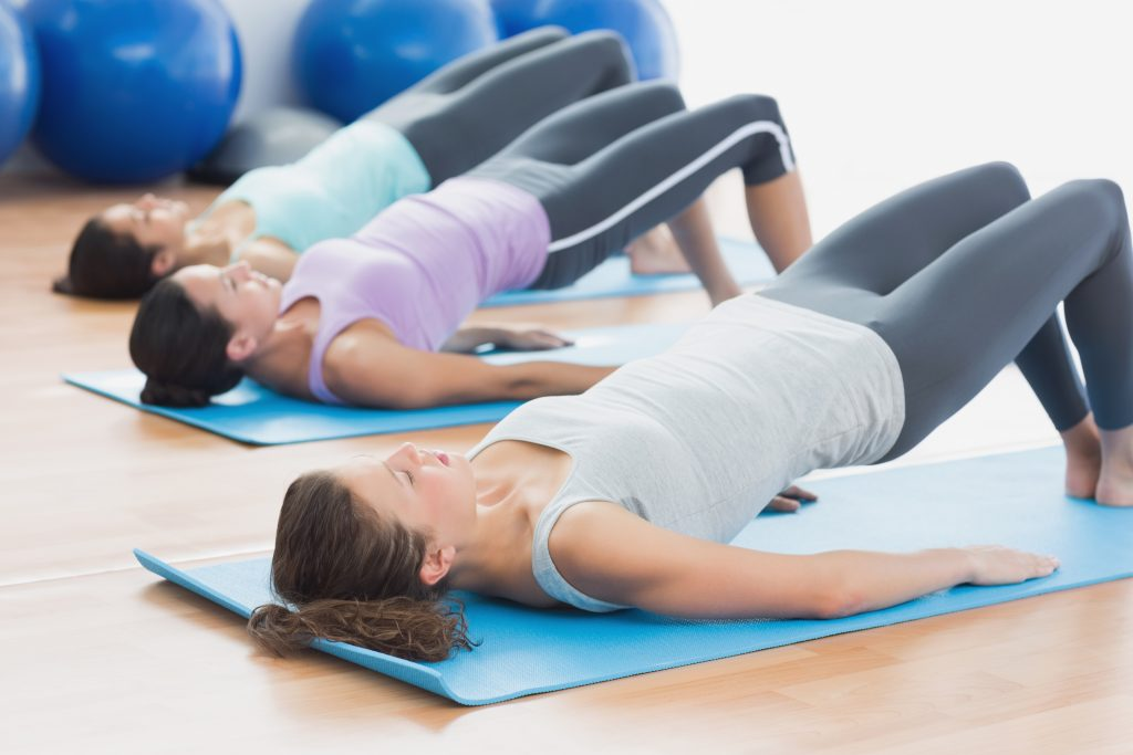 women doing pilates on mat